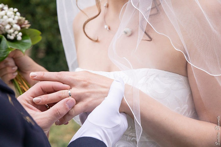 Marie enfilant alliance au doigt de la mariee